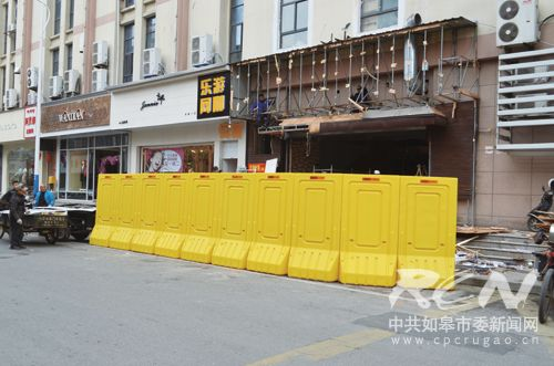 市环卫处渣土科执法人员在宁海路一家刚开始装修的店铺前设置围挡图片