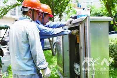 图为昨日中午12时供电公司抢险小组工人仍在户外抢修小区电路.