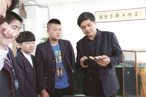 姜国圣在如皋市第一中专给学生们讲解木雕制作技艺1