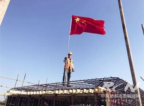 """图为工作人员把红旗插上工地。日前,万贯国际交通重点工程""""通皋大道""""工地上,参加建设的工人们早早燃起了鞭炮,祝福祖国的生日,并且在工地的一些节点插上了鲜艳的五星红旗。"""